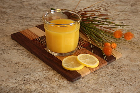 clear drinking glass with fruit juice and sliced lemon on brown wooden board