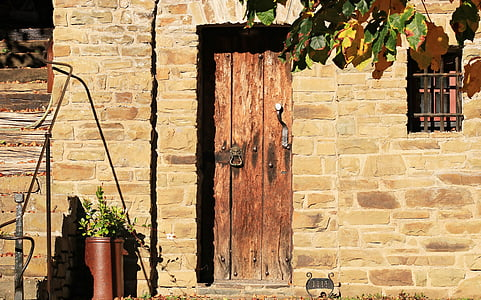 photo of brown wooden closed door with brick wall frame