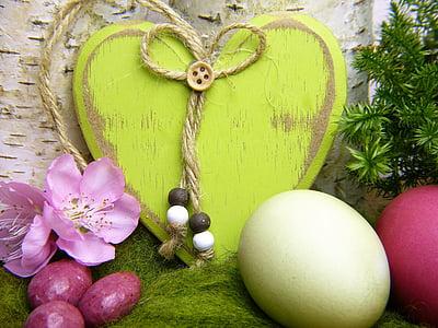 green wooden heart decor beside chicken egg and purple flowers