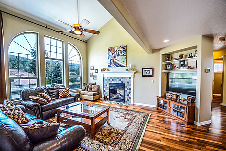 living room with sofa, coffee table, fireplace, television, and TV stand