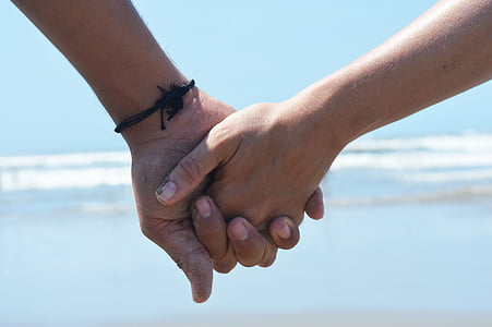 photo of holding hands near seashore