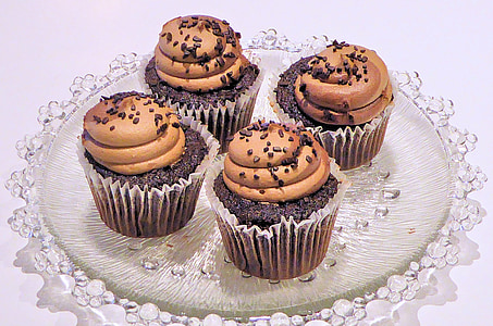 four black-and-brown cupcakes on glass tray