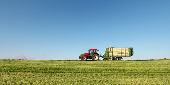 red tractor with green trailer on wide grass field