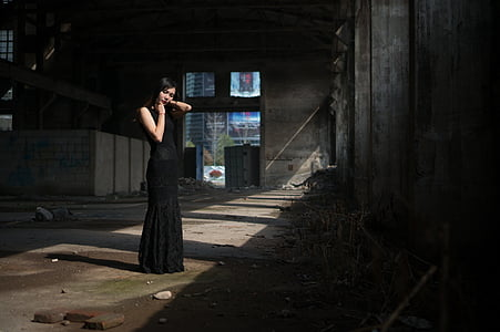 standing woman with black sleeveless dress inside building