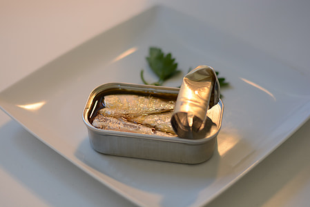 opened sardine can near parsley leaves