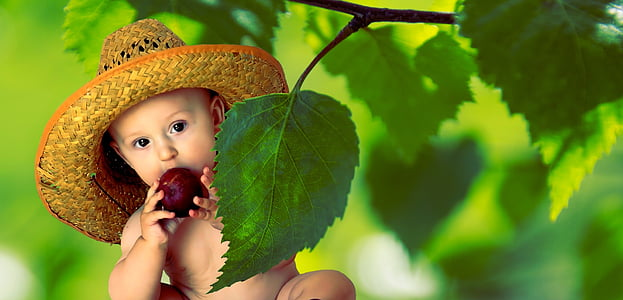 baby wearing straw hat eating fruit