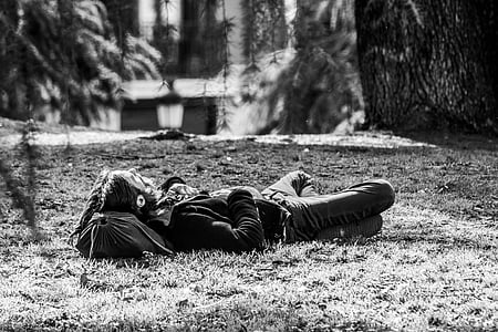 grayscale photo of man lying on grasses