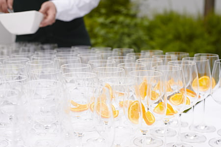 pile of clear champagne glasses near plants