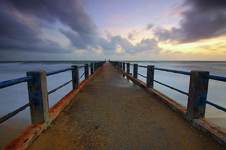 brown concrete dock beside blue ocean water under blue sky during sunrise