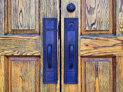 brown wooden doors with two blue metal door handles