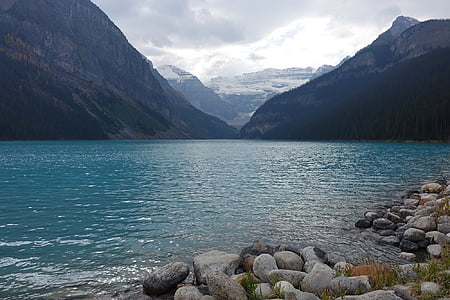 body of water near mountains at daytime