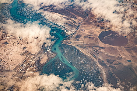 aerial photography of river between brown terrains