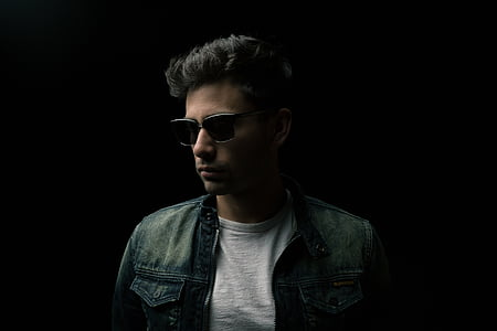black haired man in blue denim jacket and black sunglasses