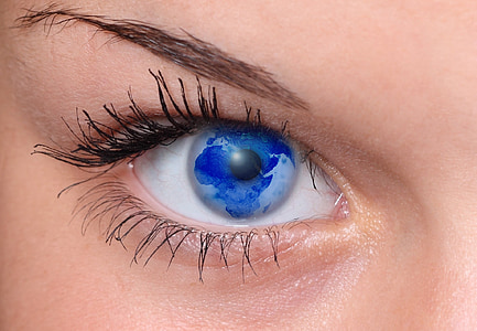 close-up photo of woman's eyes with blue earth reflection