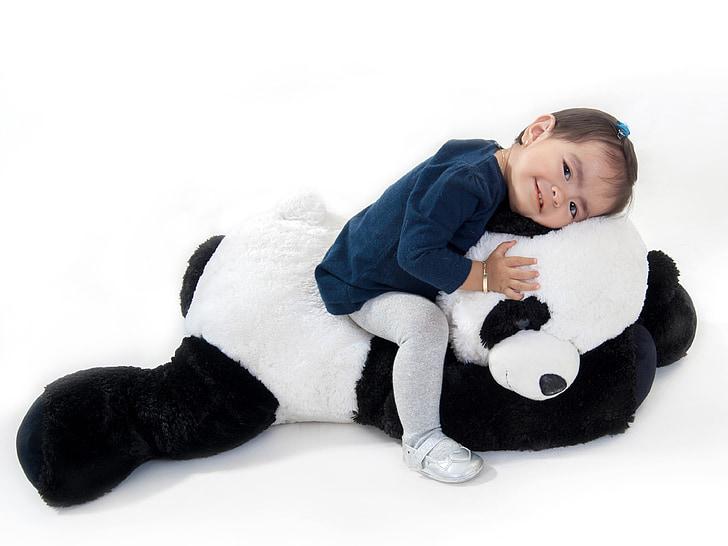 girl sitting on panda plush toy