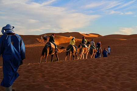 people riding on horse on desert under blue cloudy sky during daytime