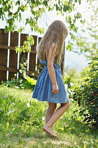 girl in blue chambray dress stands on green grass field at daytime