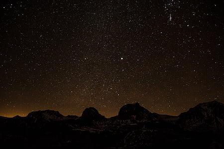 silhouette of boulder under star night