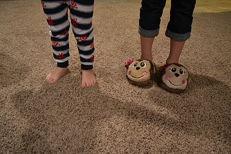 two children standing on brown rug