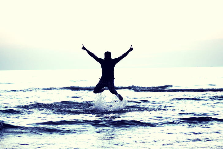 photo of man jump on sea during daytime