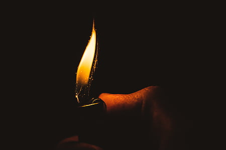 person holds lighted lighter