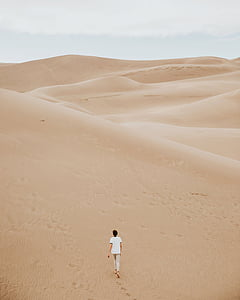 person in white shirt and gray bottoms walking at dessert