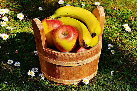 banana and apple fruit in barrel at daytime