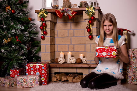 girl holding a Christmas gift near fireplace mantel