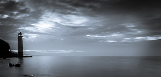 greyscale photography of lighthouse near ocean