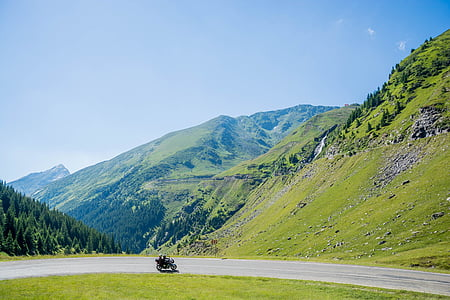 two person riding on motorcycle near mountain
