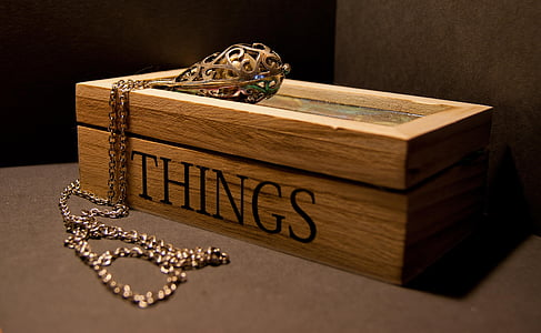 gold necklace on brown wooden Things-printed box