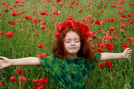 girl in green and black shirt standing on red petaled flowers field