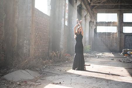woman wearing black sleeveless dress raising her arms during daytime