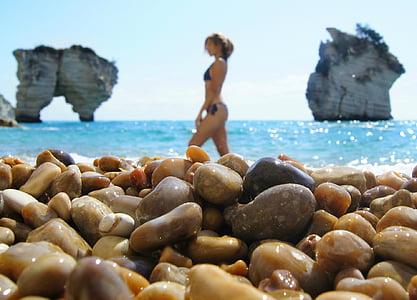 woman walking on beach shore under clear skies