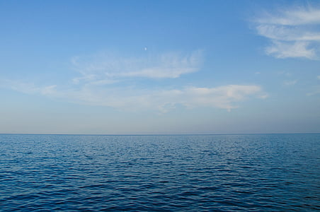 calm water overlooking horizon under cloudy sky at daytime