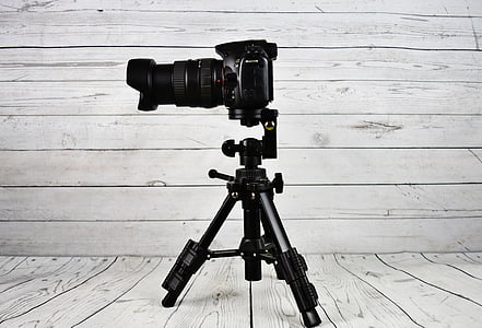 black DSLR camera beside tripod