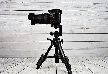 black DSLR camera beside tripod