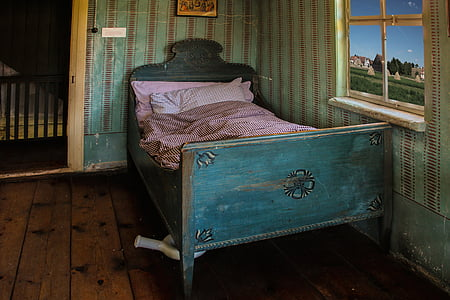 closeup photo of teal bed with pink bed sheet near window