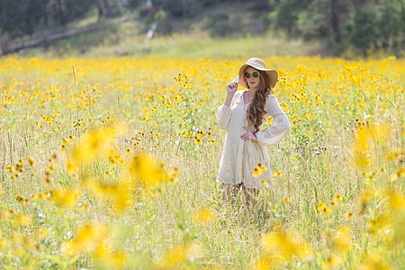 woman in white long-sleeved dress and hat standing in field of yellow flowers