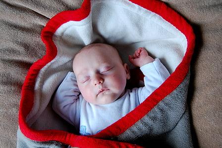 baby sleeping in sling carrier