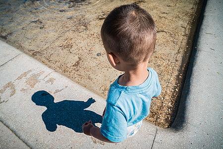 boy looking at shadow on sidewalk