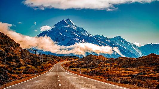 brown roadway beside brown mountain