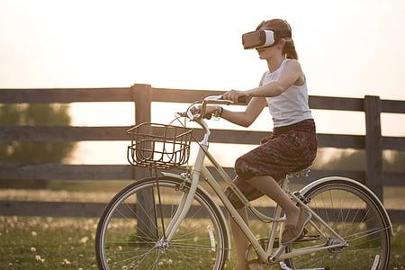 photograph of girl ride on female beach cruiser bike with VR headset