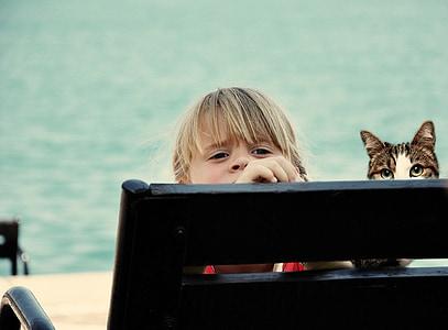 girl sitting next to cat