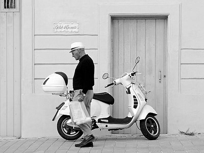 grayscale photography of man standing near motor scooter