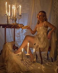 woman wearing white spaghetti strap dress holding white textile