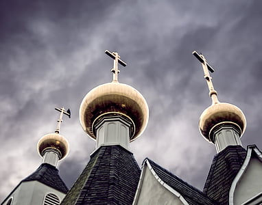 low angle photography of three gray towers with crosses under cloudy sky
