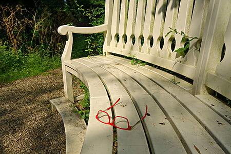 eyeglasses on white wooden bench