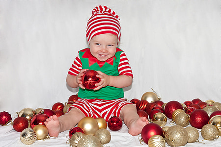 baby playing gold and red baubles
