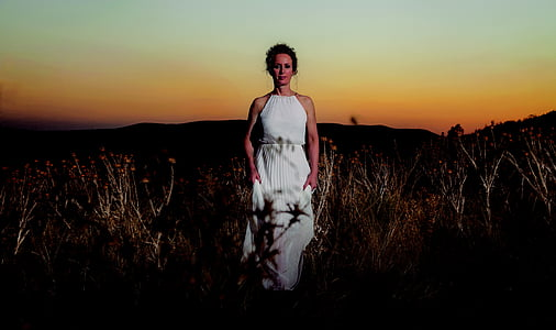 woman standing on grass wearing white dress during dawn